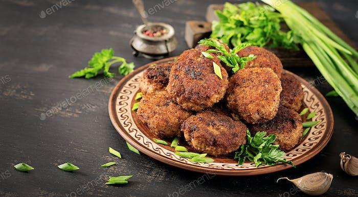 Saftige leckere Fleischkoteletts auf einem dunklen Tisch. Russische Küche.