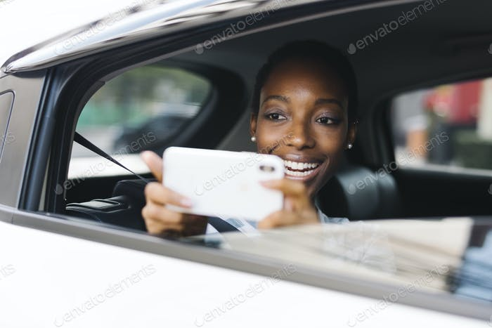 Cheerful woman in a car taking a photo of outside