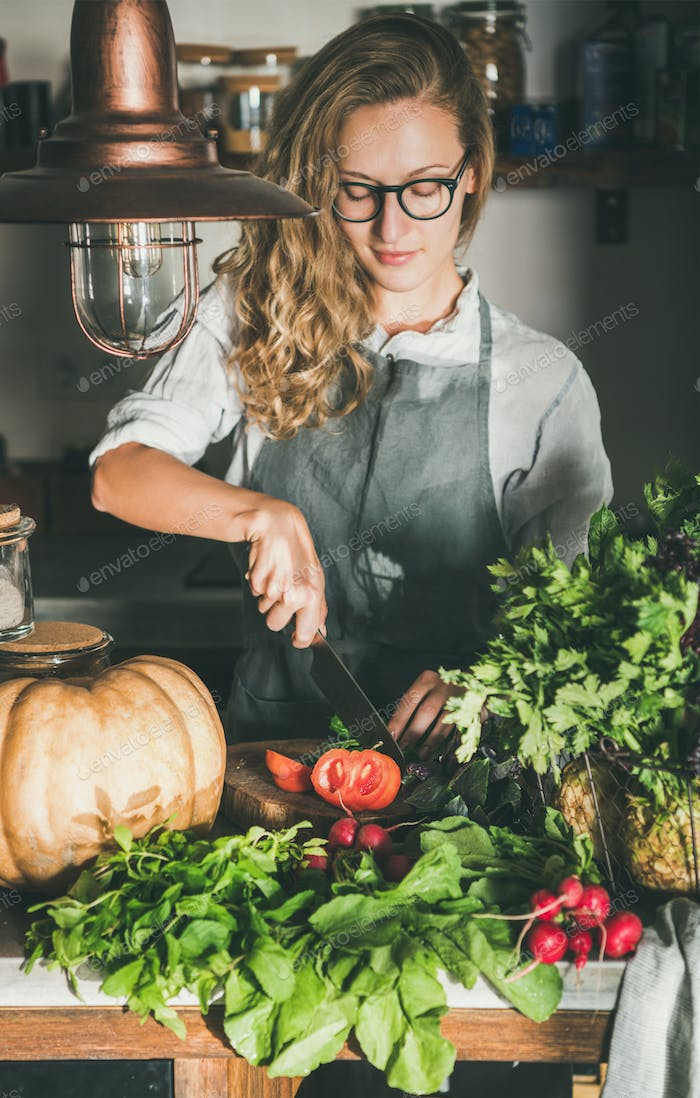 Young woman cutting fresh herbs and vegetables for cooking