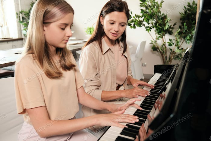 Cute teenage girl with long blond hair sitting by piano next to her mother