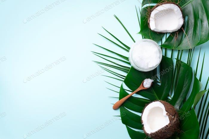 Kokosöl und reife Kokosnüsse, tropische Palmen und Monsterablätter auf blauem Hintergrund mit Kopierraum