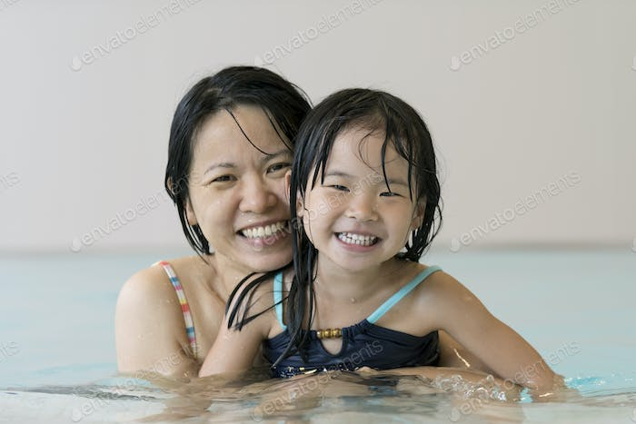 Happy mother and baby daughter at swimming pool