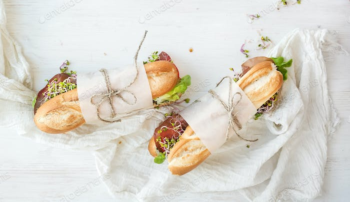 Sandwiches with beef, fresh vegetables and herbs over white wood backdrop