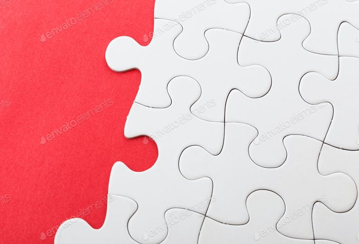 Unfinished puzzle over red background