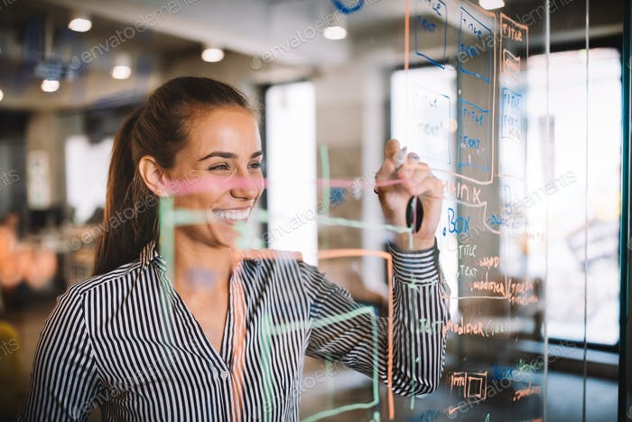 Woman working and writing on the glass board in office. Business, technology, research concept