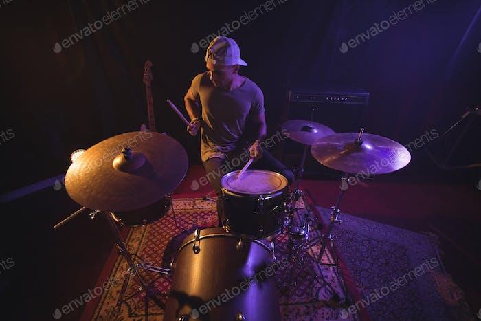 Männlicher Schlagzeuger tritt im Nachtclub auf