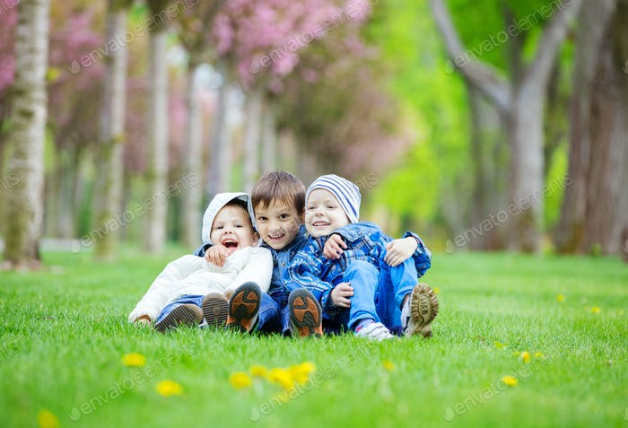 Young boys sitting on grass in park and laughing