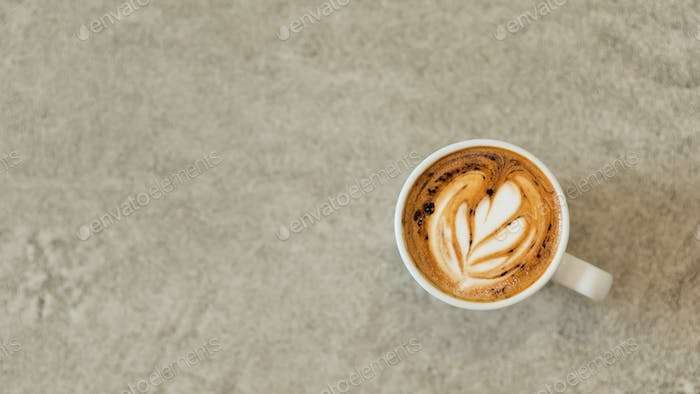 Heart shaped coffee latte stacked in white glass on a concrete floor.