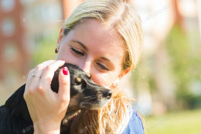 Concept of pets and happy owner - woman is holding a dog outdoors.