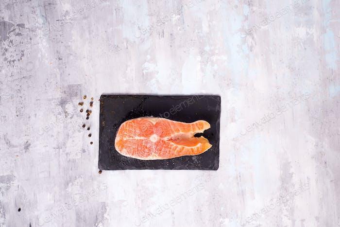 Raw salmon filet on dark slate cutting board. Lean proteins.