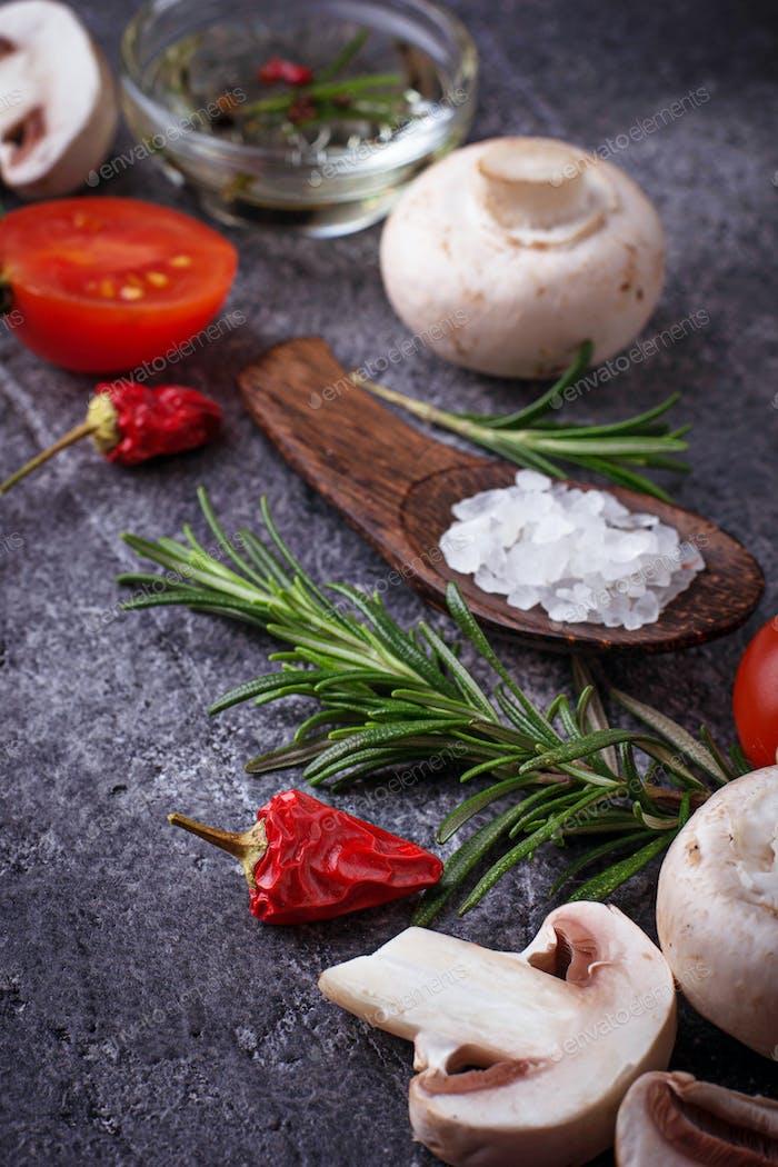 Mushrooms, tomatoes, rosemary, salt and oil. Food background