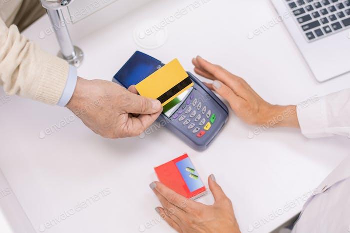 Übersicht der Hände des Seniorenkäufers, der Kreditkarte über den Bildschirm des Terminals hält