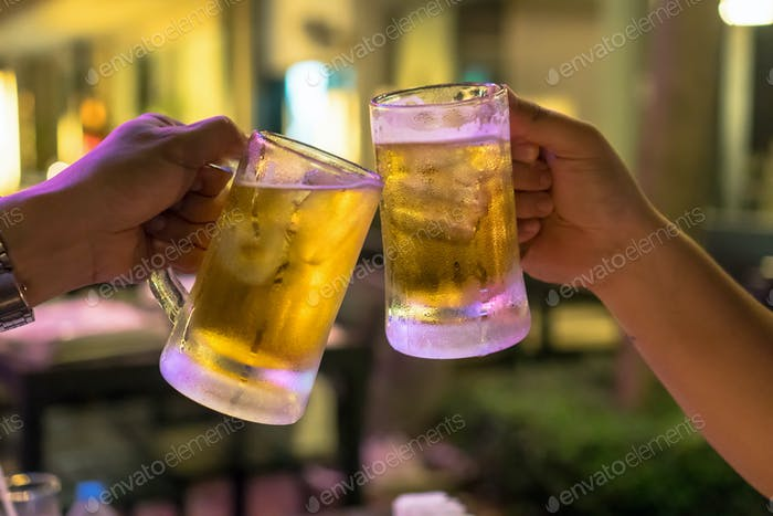 Two Glasses of Beer cheers together between friend in the low light bar and restaurant.