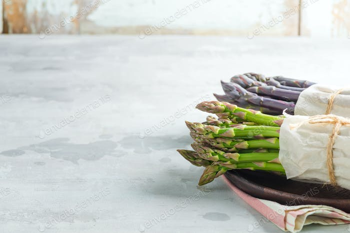 Organic food. Healthy food cooking concept. Fresh natural green and purple organic asparagus spears