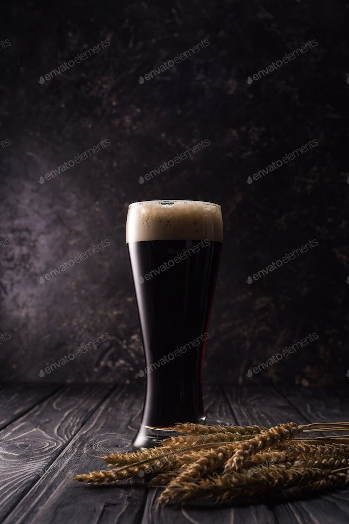 Glass of Beer With Foam Near Wheat Spikes on Wooden Table