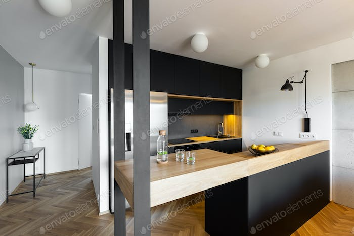 Beige countertop in black and white kitchen interior of house wi