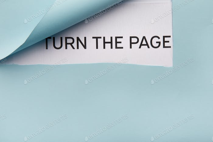 Text Turn the page on white paper behind blue folded corner