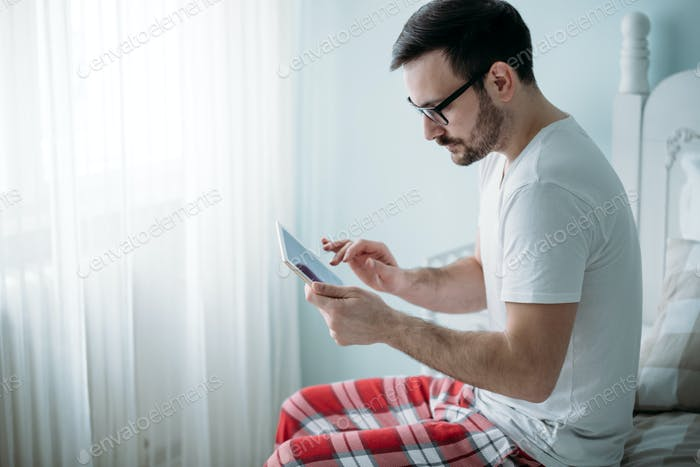 Handsome man using digital tablet in bedroom