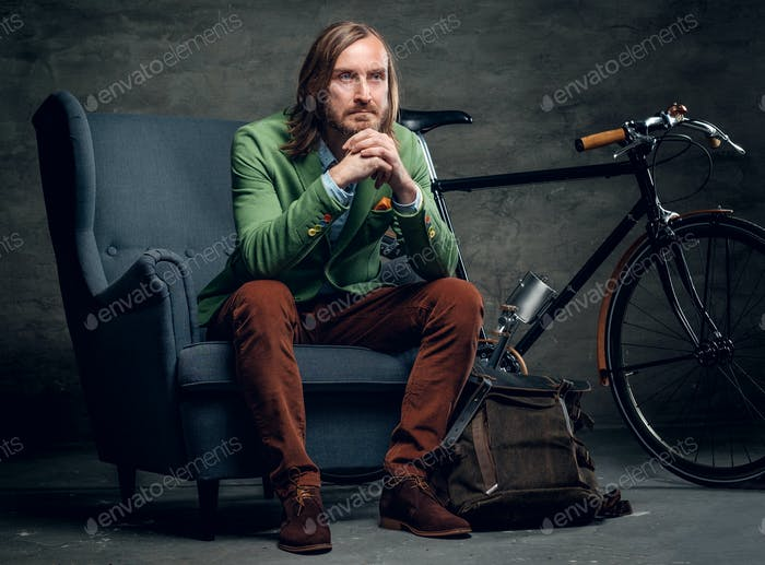 A man dressed in a green jacket sits on a chair with single spee