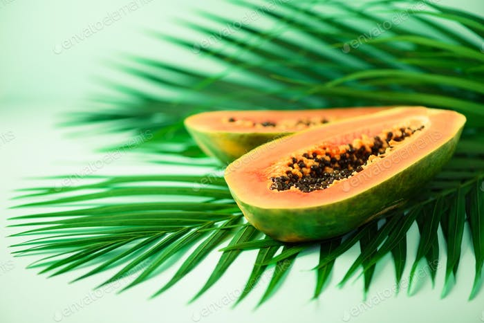 Exotic papaya fruit over tropical green palm leaves on turquoise background. Copy space. Pop art