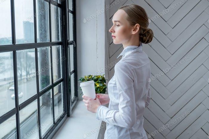 Una mujer bebiendo café en casa.