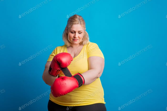 Portrait of a happy overweight woman putting on boxing gloves in studio.