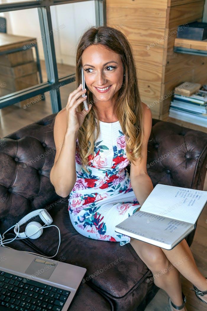 Geschäftsfrau arbeitet mit Laptop und telefoniert auf dem Sofa