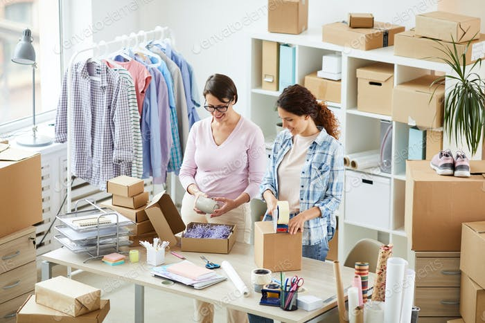 Two contemporary women packing online orders of clients in office