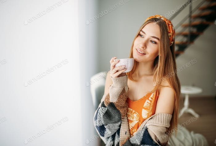 Beautiful smiling girl in knitted cardigan with cup of tea near window at home