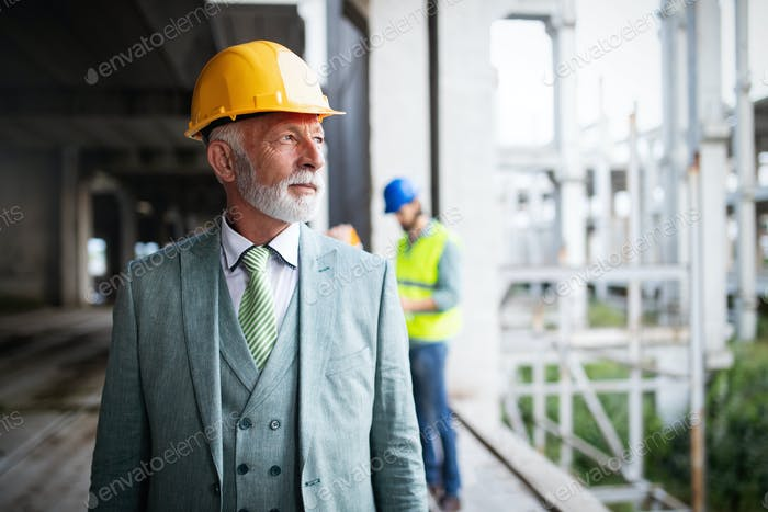 Portrait of an handsome senior engineer, architect, businessman on construction site
