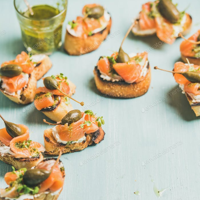 Crostini with smocked salmon, pesto sauce, watercress, capers. Square crop