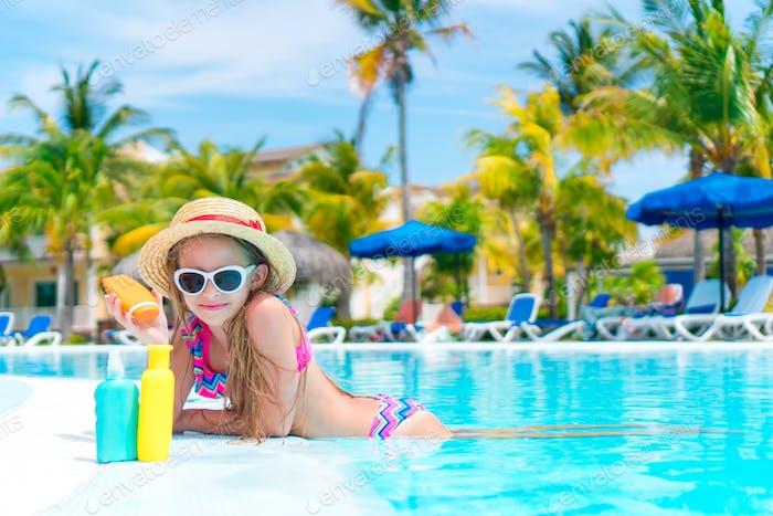 Kleines Mädchen mit Flasche Sonnencreme im Schwimmbad
