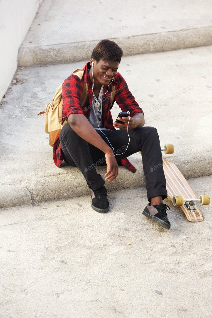 Young african man sitting outside on steps and listening to music