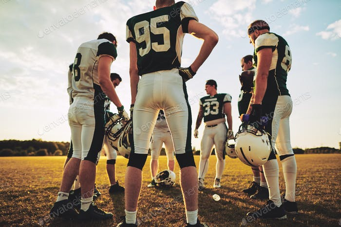American football players standing in a circle during practice