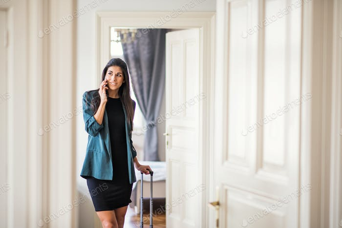 Young businesswoman on a business trip standing in a hotel room, using smartphone.
