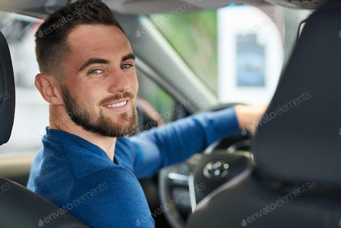 Happy man in car in dealership