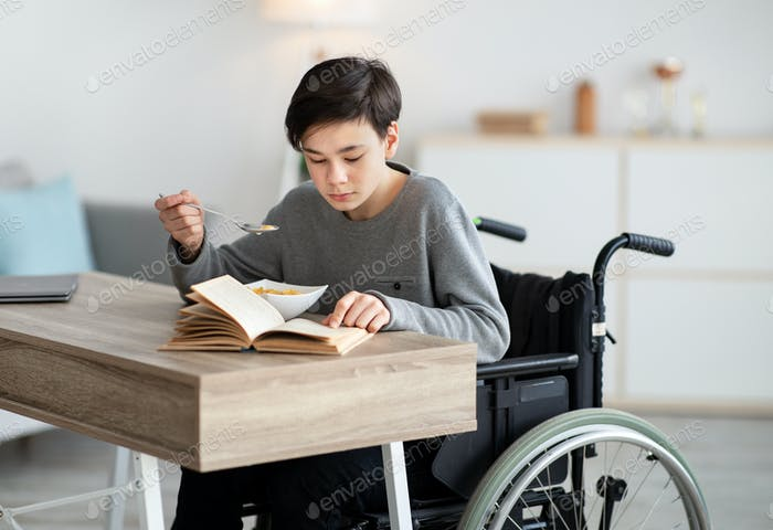 Positive impaired teenager in wheelchair having breakfast and reading book at home. Stay home