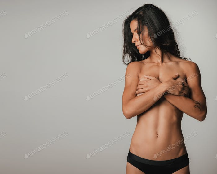 Fit partially nude woman looking sideways