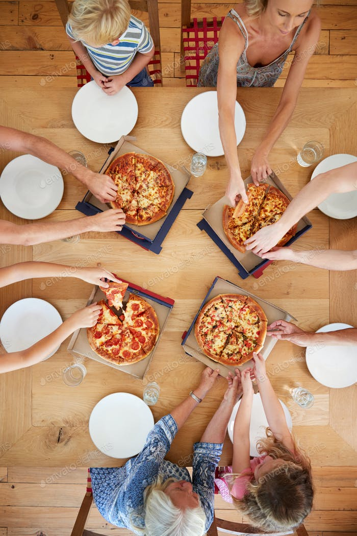 Overhead View Of Multi Generation Family Sitting Around Table Eating Pizza Together
