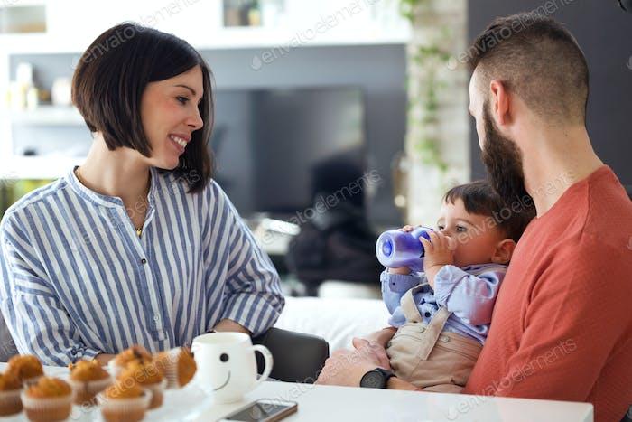 Hübsche junge Eltern suchen das Baby, während er Wasser mit Fütterungsflasche zu Hause trinkt.