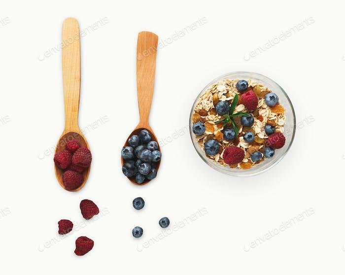 Gesunde morgendliche Mahlzeiten Hintergrund. Leckere Zutaten in Holzlöffel auf weiß isoliert