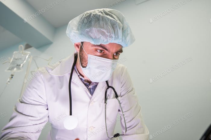 Close up of a male doctor wearing mask to protect from airborne respiratory diseases such as the flu