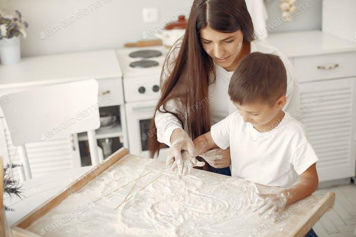 Family sitting in a kitchen and cook the dough for cookies