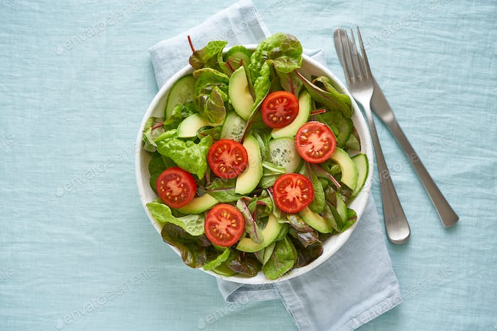 Vegan salad with tomatoes, cucumbers, avocado on pastel linen tablecloth