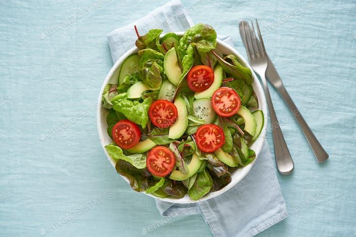 Ensalada vegana con tomates, pepinos, aguacate en mantel de lino pastel