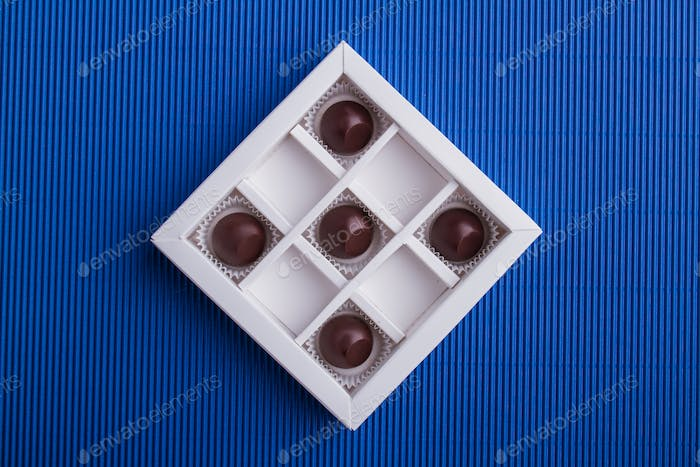 Five brown chocolate candies in the box on blue background.