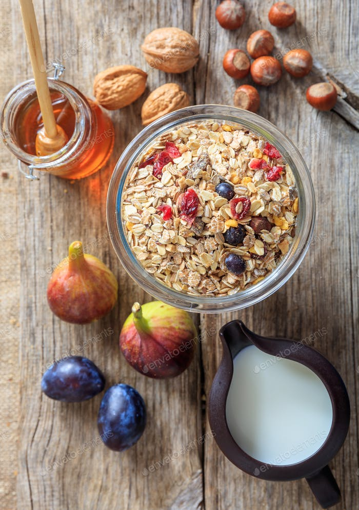 Breakfast concept. A jar with oatmeal, fruits and nuts on wood