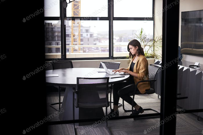 Millennial white creative businesswoman working alone in a meeting room, seen from doorway