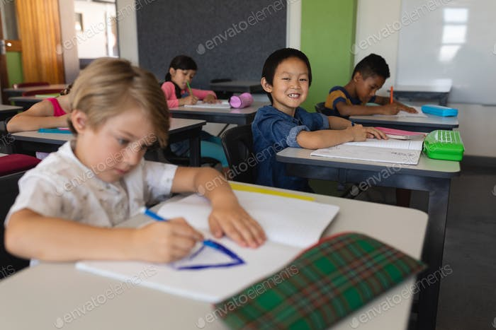 Schoolboy looking at camera while studying in classroom sitting at desks in school