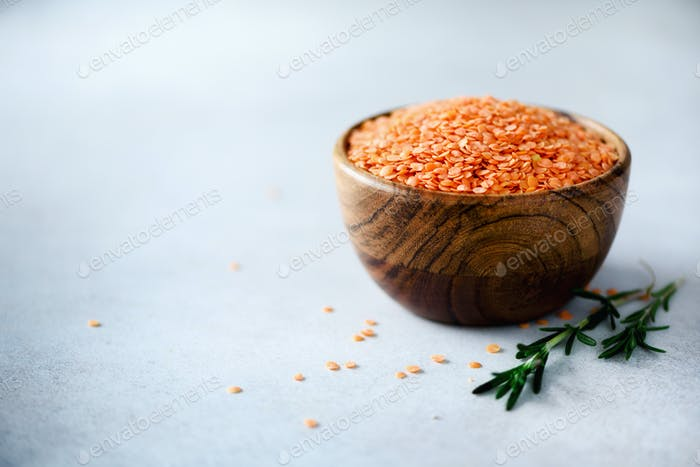 Red lentils in wooden bowl and rosemary on grey background. Healthy food ingredients. Copy space